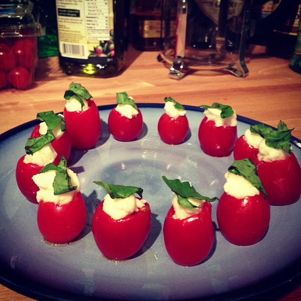 Cherry tomatoes stuffed with olive oil, mozzarella cheese, and topped with basil.